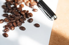 Coffee bean. Coffee bean and black pen on white paper book over brown texture table top royalty free stock images