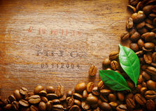 Coffee bean border on wood. Coffee bean border on an old wood surface with stamped numbers from a shipment of coffee beans with two green leaves royalty free stock image
