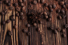 Coffee bean, cocoa powder, cinnamon and star anise on dark wood. En table Royalty Free Stock Images