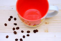 Coffee Bean with Coffee Orange Cup. On Table Wood Royalty Free Stock Photography