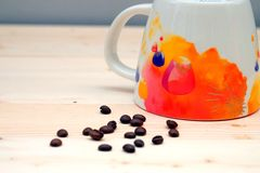 Coffee Bean with Coffee Orange Cup. On Table Wood Stock Photography