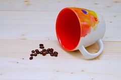 Coffee Bean with Coffee Orange Cup. On Table Wood Stock Photos