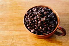 Coffee bean in the cup. Coffee bean in the wooden cup stock photos