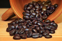 Coffee bean in earthenware cup. On wooden table stock photography