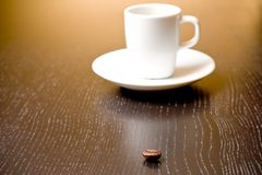 Coffee bean in front of unfocused cup of coffee Royalty Free Stock Photo