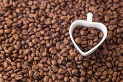 Coffee bean and heart shape cup on coffee bean background. For valentine day. Stock Photo