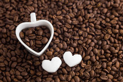 Coffee bean and heart shape cup on coffee bean background. For valentine day. Royalty Free Stock Image