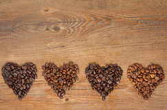 Coffee Bean Hearts. Overhead view of several varieties of fresh roasted coffee beans on a brown wooden background with copy space stock photos