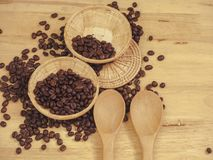 Coffee bean in little basket and spoon wood on slat wood stock photo