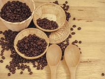Coffee bean in little basket and spoon wood on slat wood royalty free stock images