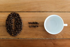 Coffee bean sign made from roasted coffee beans and white cup. On wooden backgound Stock Images