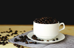 Coffee bean in white cup. Black seed coffee in white cup on wood table royalty free stock photography