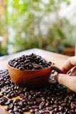 Coffee bean and wooden cup. On table stock image