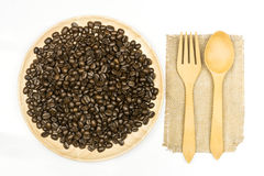 Coffee bean in wooden plate. And spoon and fork on white background Stock Photos