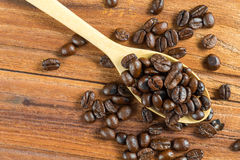 Coffee bean on wooden spoon, wooden table background Stock Photos