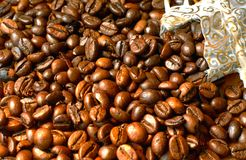 Coffee beans. Fresh roasted coffee beans in a gold silk bag stock image