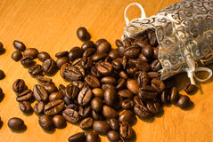 Coffee beans. Fresh roasted coffee beans in a gold silk bag royalty free stock photo