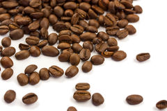 Coffee Beans. Brown coffee beans spilled out against a white surface Stock Photos