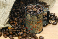 Coffee beans. Measuring cup  and a burlap bag with coffee beans Stock Photography