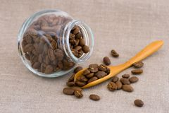 Coffee beans. Spilling out of glass jar royalty free stock photography