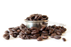 Coffee Beans. Whole coffee beans spilling out of a full coffee measure. Shot on white background. Focus is on the edge of the cup. Beans in the foreground are Stock Photography
