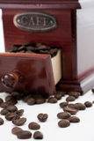 Coffee beans. Dispersed coffee beans with coffee grinder in the background Royalty Free Stock Photography