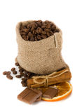 Coffee beans. In canvas sack with cinnamon, chocolate and dried orange slice Stock Photo