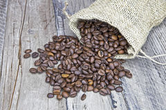 Coffee beans. In a jute bag on a wooden table Royalty Free Stock Image