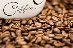 Coffee beans. Photo of roasted coffee beans and cup with the text coffee Royalty Free Stock Images