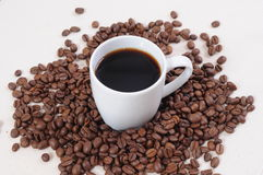 Coffee and beans. White cup with coffee and beans surrounded on white backdrop Royalty Free Stock Photography