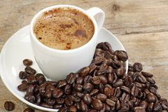 Coffee with beans. Milky coffee with coffee beans on a wooden table Stock Photos