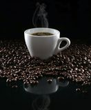 Coffee and beans. Hot cup of coffee and beans on a dark background stock image