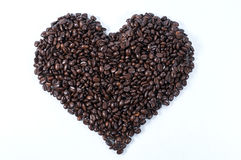 Coffee beans. Herat shape coffee beans on a white counter top royalty free stock images