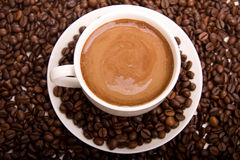Coffee and beans. A background of a coffee cup sitting in coffee beans Stock Photos