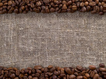 Coffee beans, against a background of burlap. Royalty Free Stock Image