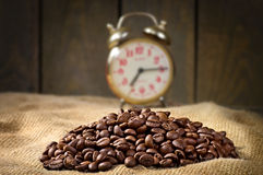 Coffee beans, alarm clock on sacking in vintage grunge style Stock Photography