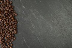 Coffee beans along a slate board Royalty Free Stock Photography