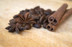 Coffee beans with anise and cinnamon on wooden background. Coffee beans with spices - anise and cinnamon - on wooden cutting board, ingredients for aromatic Royalty Free Stock Photography