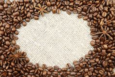 Coffee beans with anisetree stars oval frame on natural sacking background with space for your text. Colorful brown roasted coffee beans and anisetree stars Stock Photo
