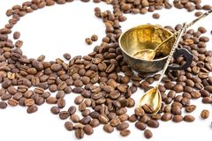 Coffee beans and antuque cup and spoons on white background. Coffee beans and antuque cup and spoons on white royalty free stock photography