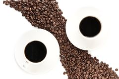 Coffee beans arranged diagonally with coffee cups on white Stock Photography