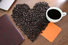Coffee beans arranged a heart shape and placed paper Notebook wi Royalty Free Stock Images