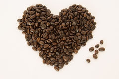 Coffee beans arranged in a heart shape on white background. Stock Photo