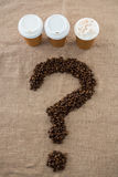 Coffee beans arranged in question mark shape with disposable coffee cups Royalty Free Stock Images