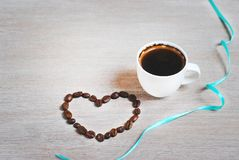 Coffee beans as a heart. cup of coffee and heart of coffee beans. Label free space stock image