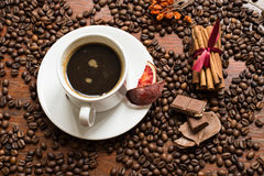 Coffee beans background with cofee cup, cinnamon, and chocolate. Wallpaper royalty free stock photo