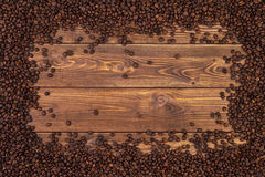 Coffee beans background. Frame of coffee beans on brown wooden table. Top view with copy space Royalty Free Stock Photography