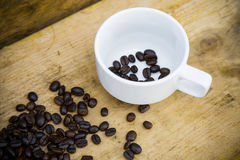 Coffee beans background on wooden, Fresh coffee beans with coffee cup on wooden background, Drinking set background Stock Images