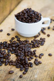 Coffee beans background on wooden, Fresh coffee beans with coffee cup on wooden background, Drinking set background Stock Photography
