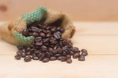Coffee beans in the bag. On the brown wood background stock images